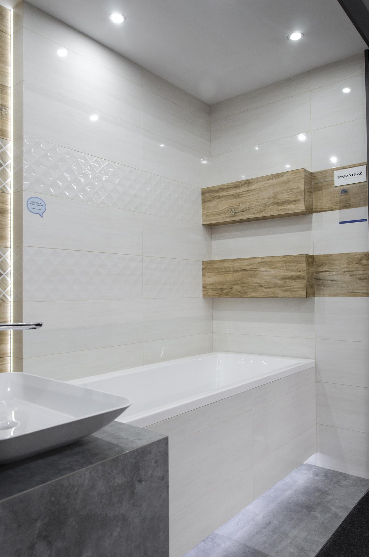 Biała łazienka z wanną w zabudowie i płytką drewnopodobną - zdjęcie od BLU salon łazienek Skierniewice
