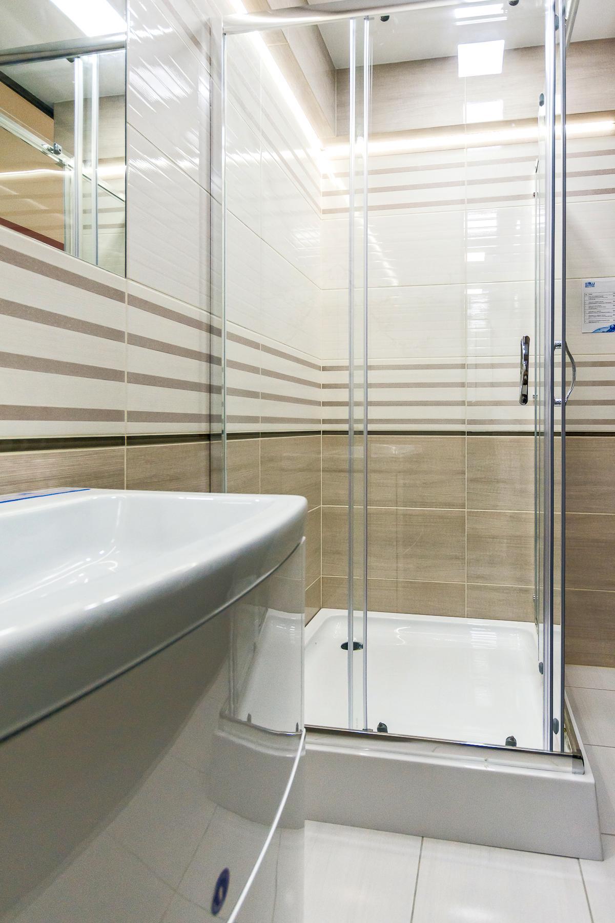 Jasna łazienka z dodatkiem płyt z wzorem drewna - zdjęcie od BLU salon łazienek Giżycko